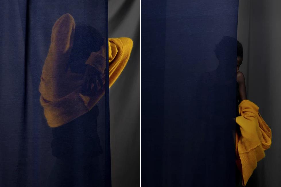 Photographie ©Artistic (in) View Studio. Jeune femme qui enlève son pull jaune, derrière un rideau bleu. Photo sombre, énigmatique et poétique