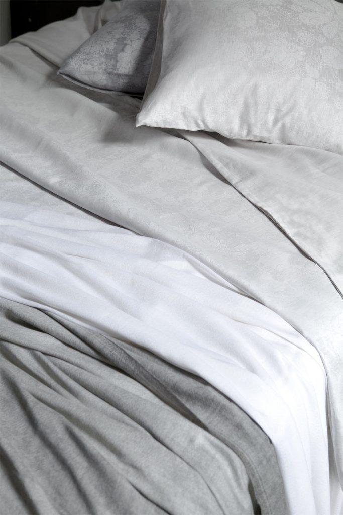 collection de drap gris noir et blanc de verilin. Lit defait avec oreillers