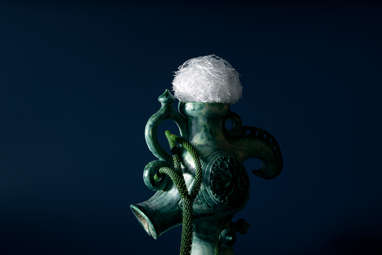 Photographie de virginie pérocheau avec une boule devermicelle de riz au-dessus d'une sculpture rappellant une ancre de marin.Fond bleu, sculpture verte