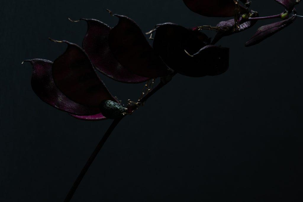 pendentif enroulé autour d'une fleur brodeau foncé en forme de haricot une photo de virginie perocheau